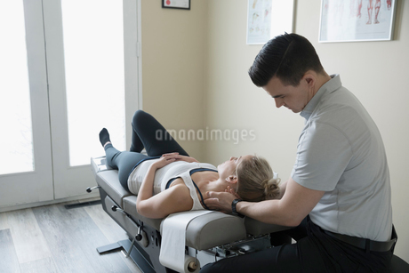 Male physiotherapist examining neck of woman on clinic examination tableの写真素材 [FYI02319062]