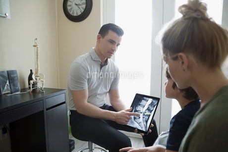 Physiotherapist showing digital x-ray on digital tablet to mother and son in clinic examination roomの写真素材 [FYI02319073]