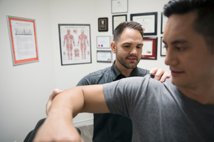 Male physiotherapist checking shoulder and arm of client in officeの写真素材 [FYI02319077]