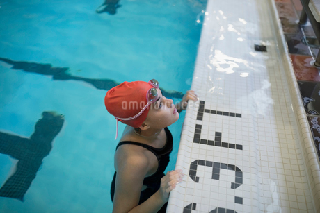 Teenage girl swimmer leaning at edge of swimming poolの写真素材 [FYI02319126]