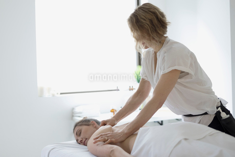 Serene woman receiving massage on spa massage tableの写真素材 [FYI02319155]