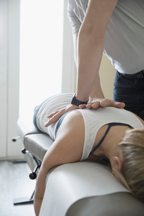 Male physiotherapist massaging back of woman on clinic examination tableの写真素材 [FYI02319198]