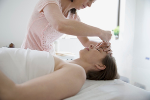 Female acupuncturist inserting needle into forehead of woman on massage tableの写真素材 [FYI02319204]