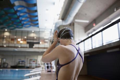 Teenage girl swimmer preparing swimming goggles at swimming poolの写真素材 [FYI02319206]