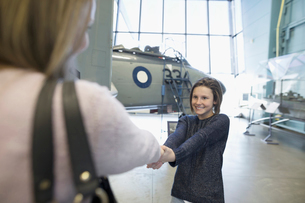 Mother and daughter holding hands next to airplane in war museum hangarの写真素材 [FYI02319209]