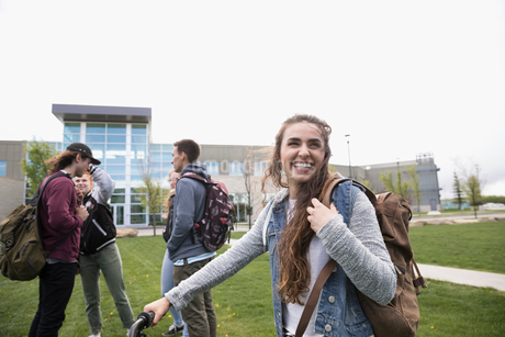 Smiling female college student with backpack on lawn on college campusの写真素材 [FYI02319247]