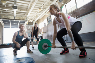 Women motivating friend weightlifting, doing barbell deadlift at gritty gymの写真素材 [FYI02319301]