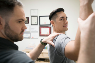 Male physiotherapist examining shoulder and arm of client in officeの写真素材 [FYI02319318]