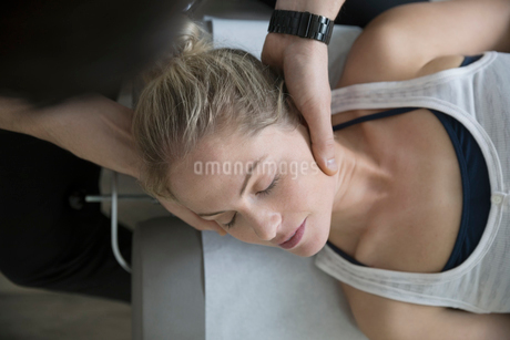 Chiropractor adjusting neck of woman on clinic examination tableの写真素材 [FYI02319420]
