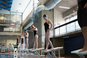 Young women swimmers ready, standing on starting platforms in swimming poolの写真素材 [FYI02319451]