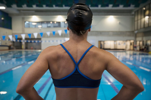 Rear view female swimmer in bikini top standing at swimming poolの写真素材 [FYI02319476]