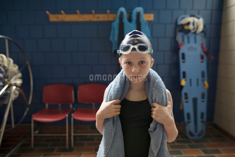 Portrait serious girl swimmer with towel around neck in locker roomの写真素材 [FYI02319489]