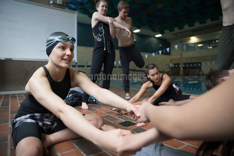 Swimming teammates helping each other stretch before practiceの写真素材 [FYI02319492]