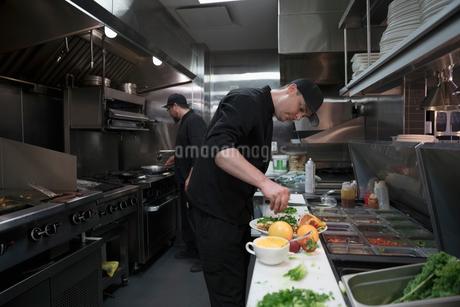 Line cook preparing food in restaurant kitchenの写真素材 [FYI02319516]