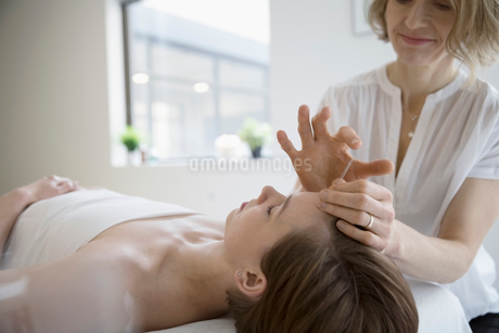 Acupuncturist applying needle to forehead of serene womanの写真素材 [FYI02319520]