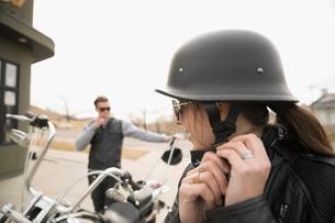 Female biker fastening helmet on motorcycle in parking lotの写真素材 [FYI02319528]
