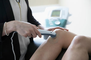 Female physiotherapist using ultrasound machine on knee of client in clinic examination roomの写真素材 [FYI02319547]