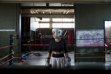 Tough female boxer looking away in boxing ringの写真素材 [FYI02319599]