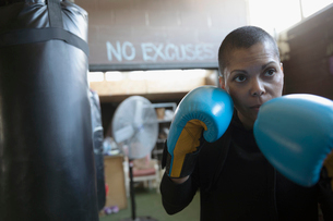 Portrait serious, tough female boxer in boxing gloves in fighting stance in gymの写真素材 [FYI02319670]
