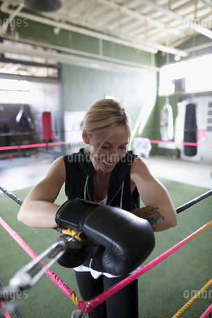 Smiling female boxer leaning on corner of boxing ringの写真素材 [FYI02319721]