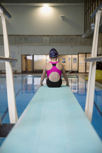 Girl swimmer sitting at the edge of springboard diving board over swimming poolの写真素材 [FYI02319725]