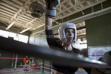 Confident, tough female boxer with arm raise in boxing ringの写真素材 [FYI02319729]