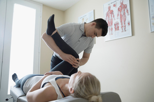 Male physiotherapist stretching leg of woman in clinic examination roomの写真素材 [FYI02319730]