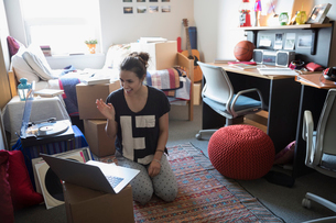 Female college student waving, video chatting with laptop in dorm roomの写真素材 [FYI02319747]