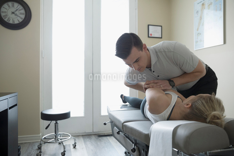 Male chiropractor adjusting woman on clinic examination tableの写真素材 [FYI02319768]