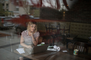 Female diner owner inputting receipts at laptopの写真素材 [FYI02319837]