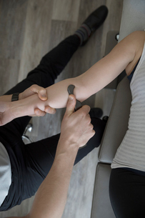 Male physiotherapist performing scraping massage on arm of woman in clinic examination roomの写真素材 [FYI02319853]