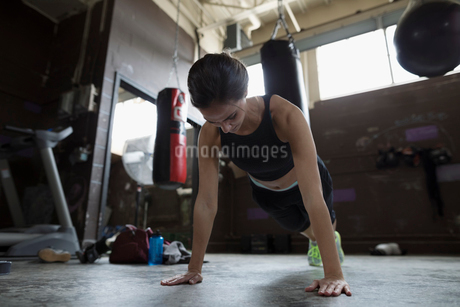Strong female boxer doing plank exercise in gymの写真素材 [FYI02319874]