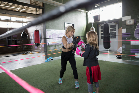 Mother boxer teaching daughter boxing in boxing ring at gymの写真素材 [FYI02319907]