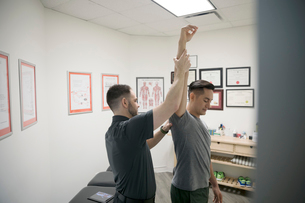 Male physiotherapist checking shoulder and arm of client in officeの写真素材 [FYI02319919]