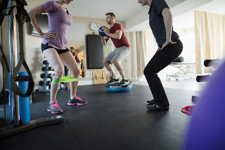 Female physiotherapist working with clients exercising and stretching in clinic gymの写真素材 [FYI02319956]
