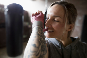 Female boxer with arm tattoo biting wrist wrap in gymの写真素材 [FYI02319961]