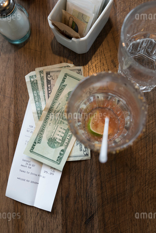 Overhead view restaurant bill and cash change on tableの写真素材 [FYI02319991]