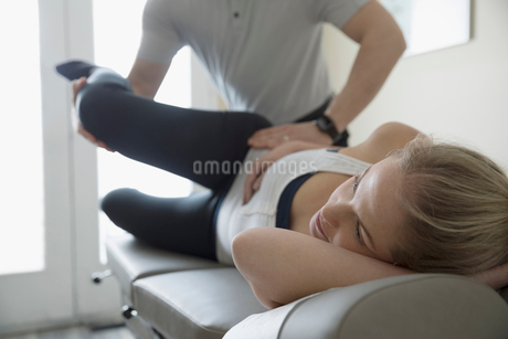 Male physiotherapist stretching leg of woman on clinic examination tableの写真素材 [FYI02320000]