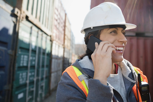 Smiling female worker talking on cell phone in industrial container yardの写真素材 [FYI02320006]