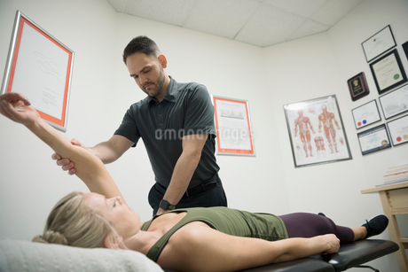 Male physiotherapist stretching arm of female client in officeの写真素材 [FYI02320032]