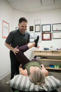 Male physiotherapist stretching leg of female client in officeの写真素材 [FYI02320033]