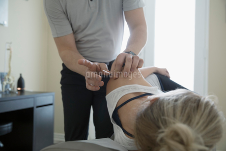 Male acupuncturist inserting needle in shoulder of woman on clinic examination tableの写真素材 [FYI02320034]