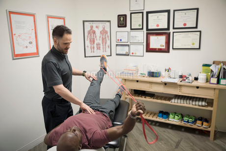Male physiotherapist helping client stretching with resistance band in officeの写真素材 [FYI02320040]