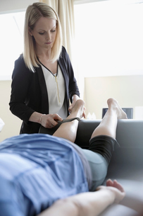 Physiotherapist performing scraping massage on calf muscle of woman on clinic examination roomの写真素材 [FYI02320063]