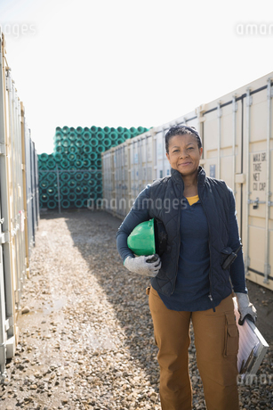 Portrait confident female African American foreman holding hard-hat and clipboard in industrial contの写真素材 [FYI02320067]