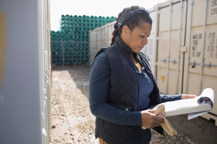 Female African American foreman reviewing paperwork at industrial container yardの写真素材 [FYI02320093]