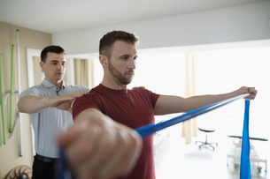 Male physiotherapist guiding client stretching shoulders with resistance band in clinic gymの写真素材 [FYI02320103]