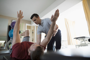 Male physiotherapist stretching client in clinic gymの写真素材 [FYI02320104]