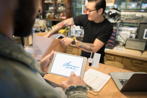Customer using touch signature on digital tablet at counter in motorcycle shopの写真素材 [FYI02320107]