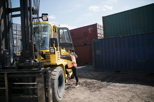 Female forklift driver in sunny industrial container yardの写真素材 [FYI02320115]